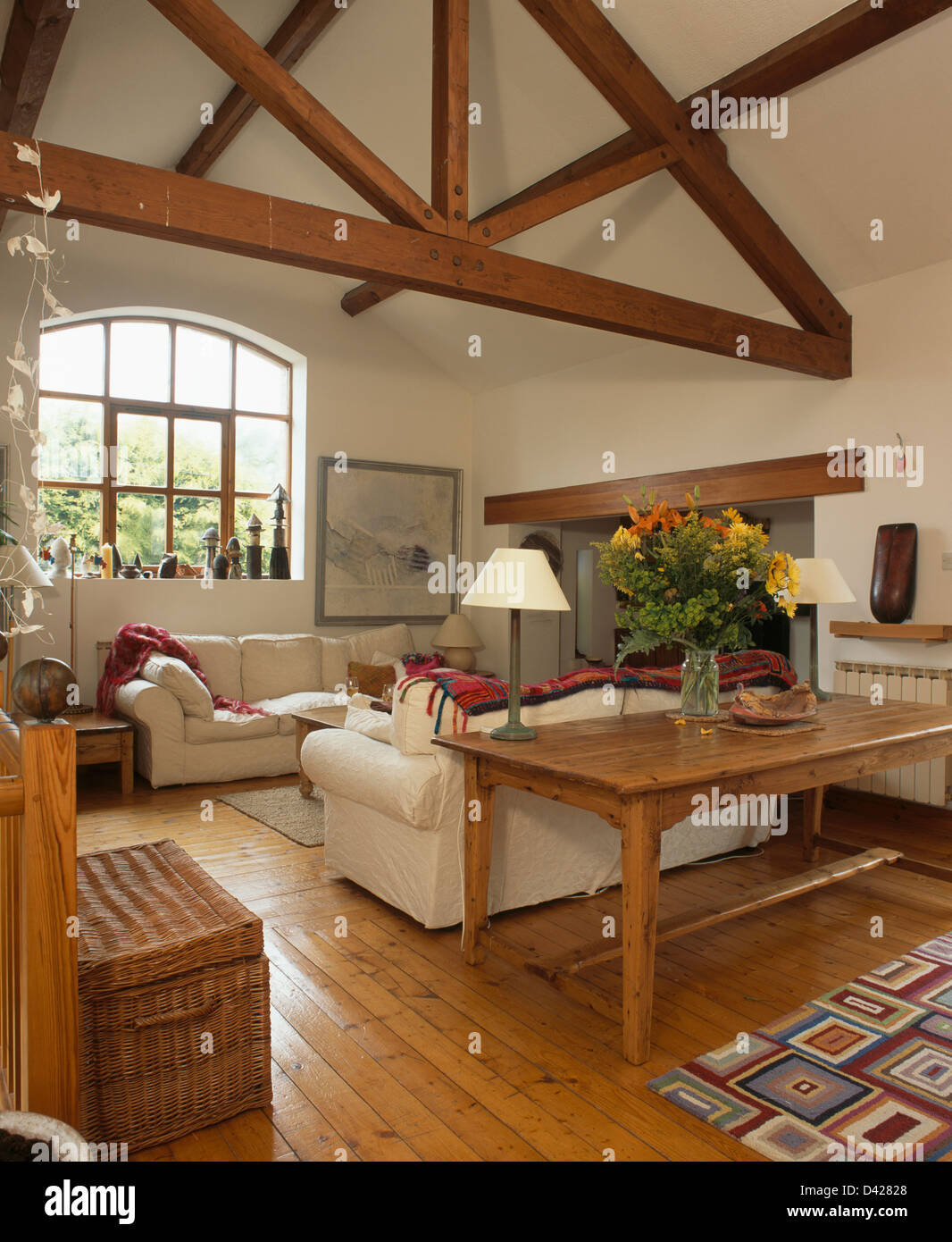Reclaimed wood table and pine flooring with white sofas in living ...