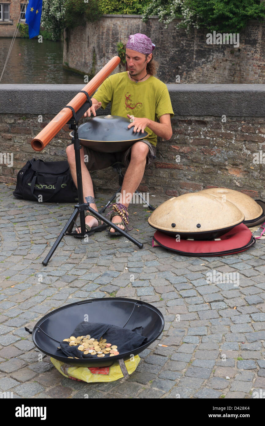 Street entertainer playing music with a pot of money in Bruges, East Flanders, Belgium, Europe. - Stock Image