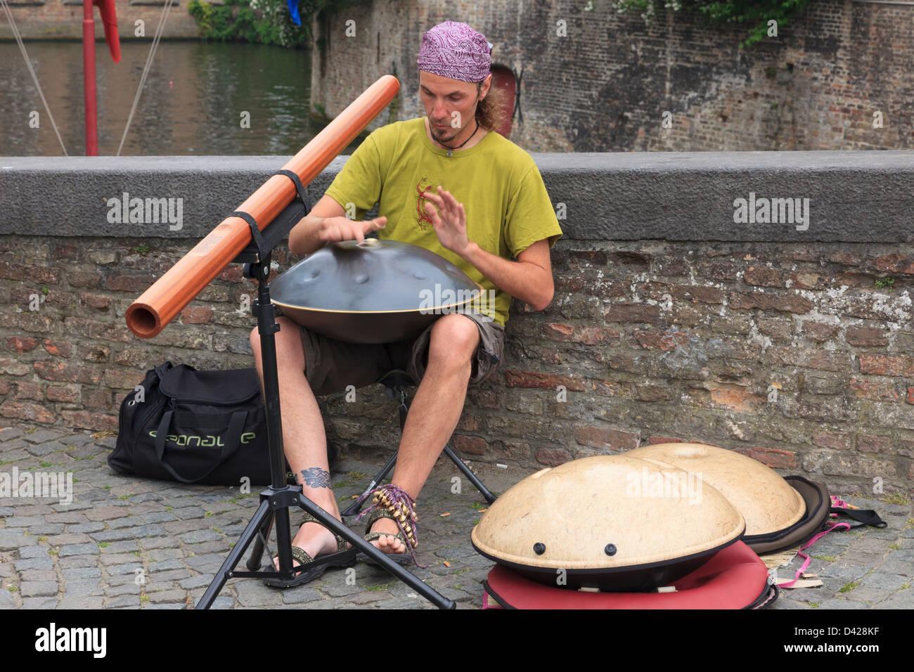 Street entertainer playing music in Bruges, East Flanders, Belgium, Europe. - Stock Image