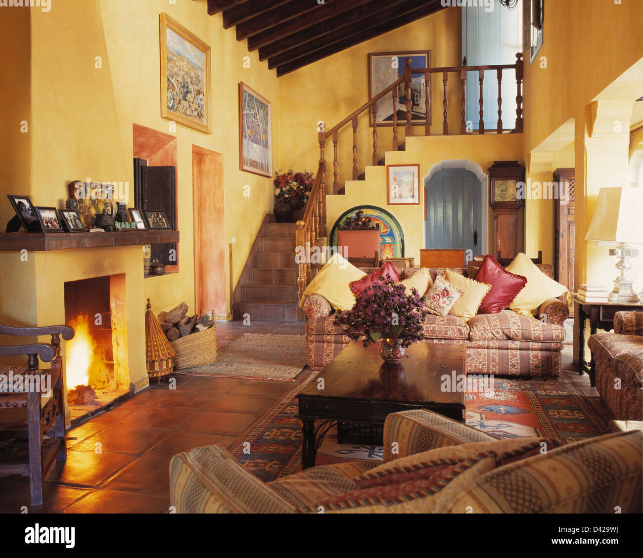. Comfortable sofas in yellow living room with lighted fire in Stock