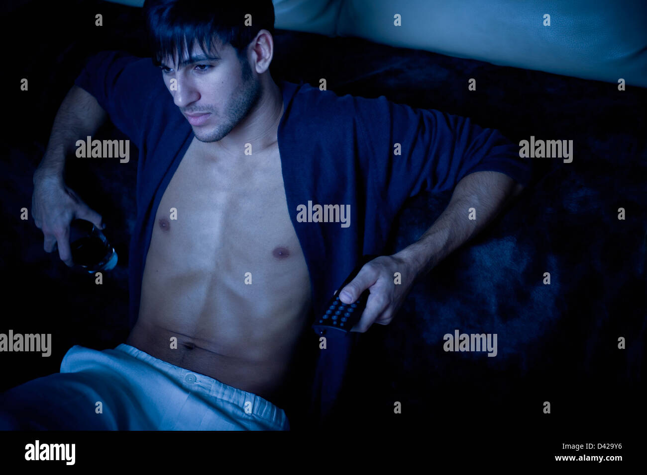 A man in his pajamas lit by the blue glow of tv, holding a remote control in one hand and a drink on the other. Stock Photo