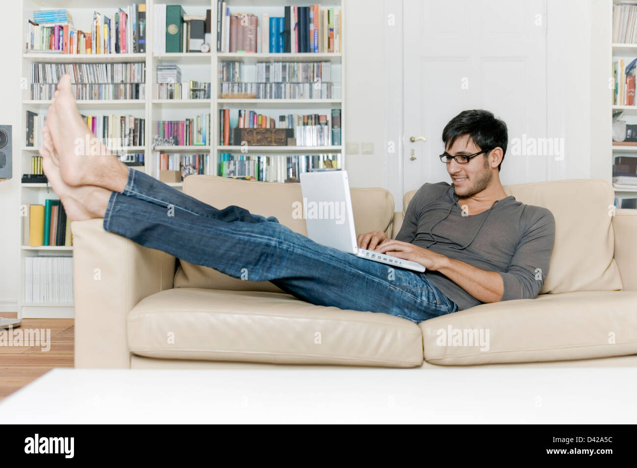 A man very comfortable surfing the internet using a laptop. - Stock Image
