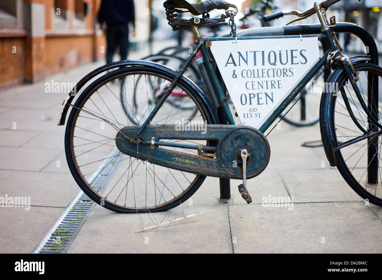 Old bicycle advertizing an antiques and collectors centre Stratford Upon Avon Warwickshire UK - Stock Image