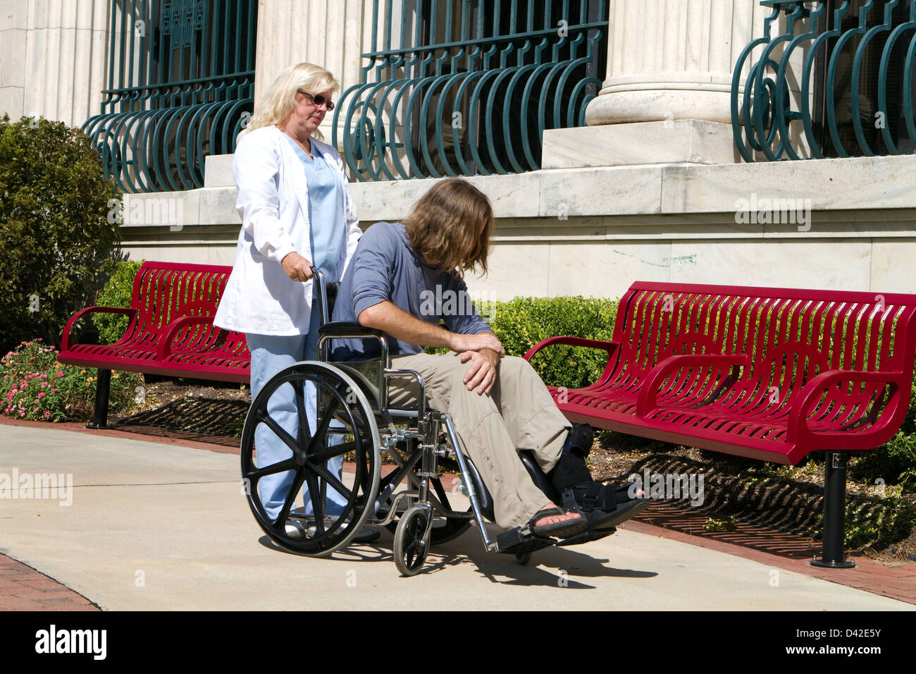 Nurse caregiver looks after a disabled psychopathic patient outside a state hospital facility for the mentally insane. - Stock Image