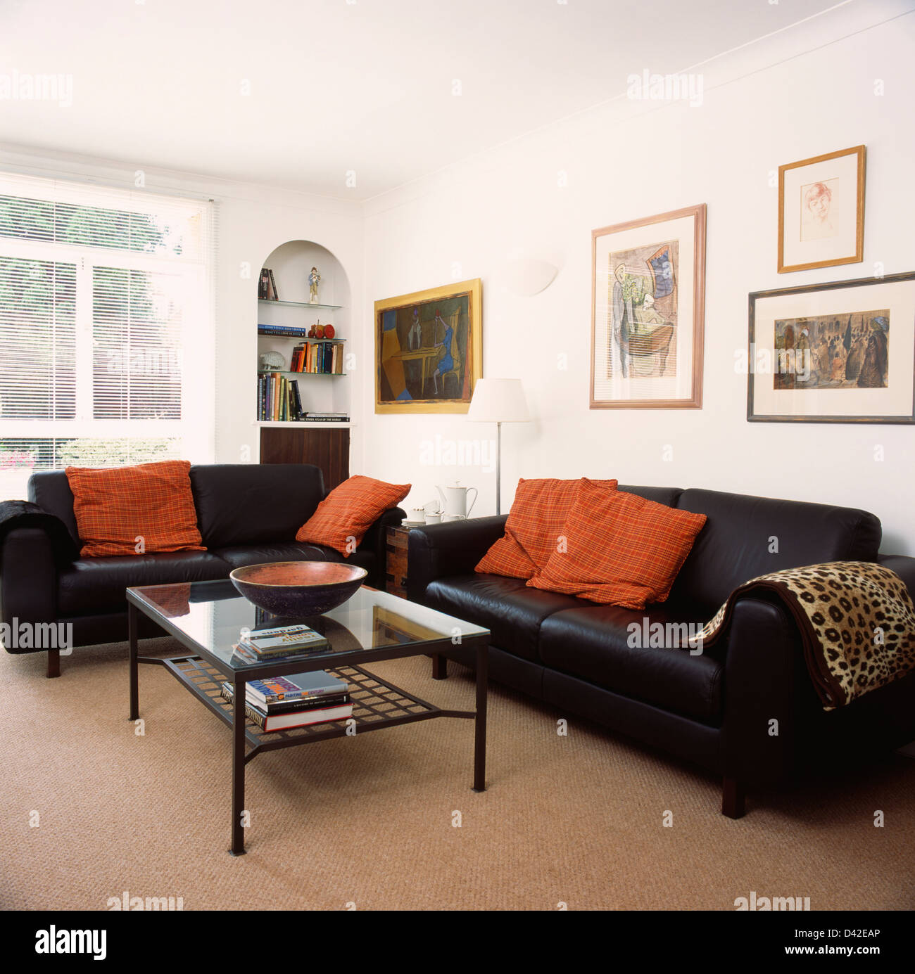 Orange Cushions On Black Leather Sofas In Living Room With Beige Carpet And  Glass Topped Coffee Table