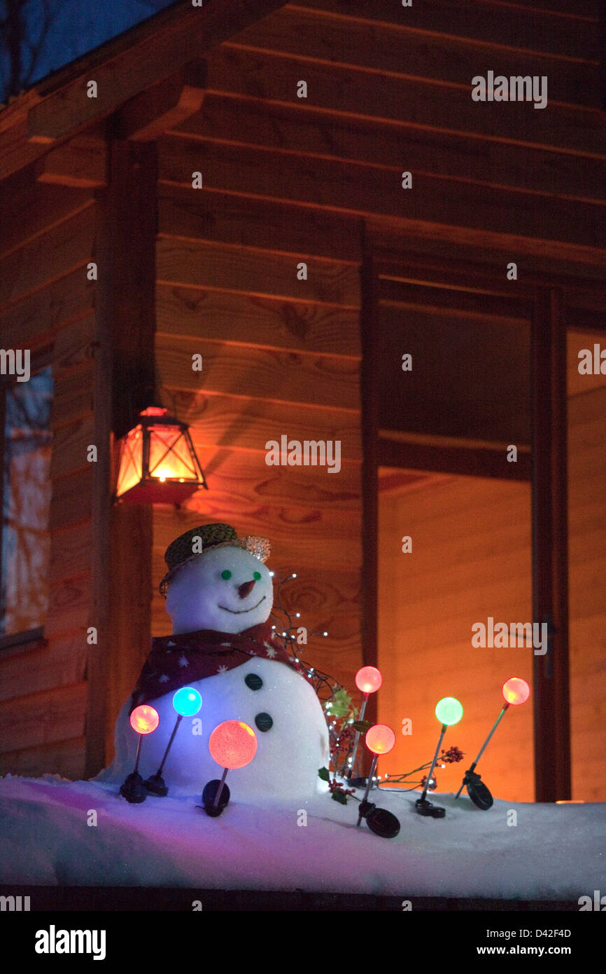 France, Ariege, snowman at night surrounded with solar garden lamps, in front of a wooden house - Stock Image