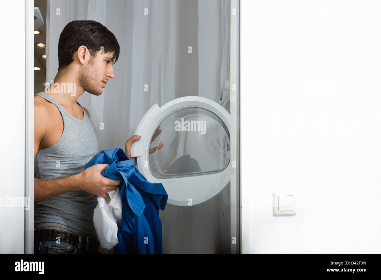 A young man unsure about doing his laundry - Stock Image