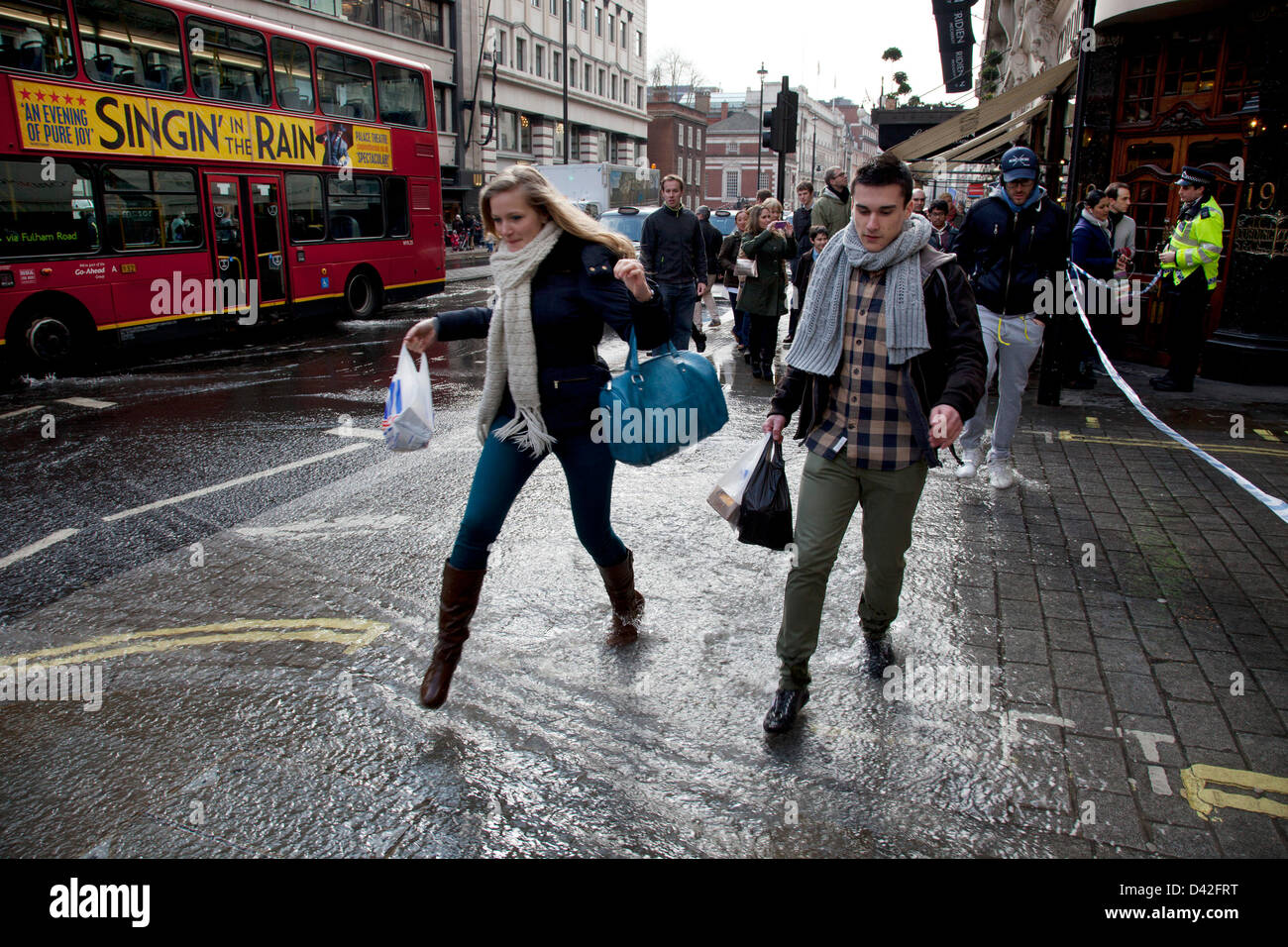 London, UK. Saturday 2nd March 2013. Burst water main causes flooding disruption in central London. People run through - Stock Image