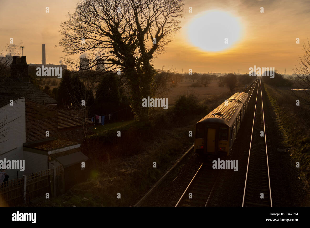 Trains converging railway lines in the evening sun. - Stock Image
