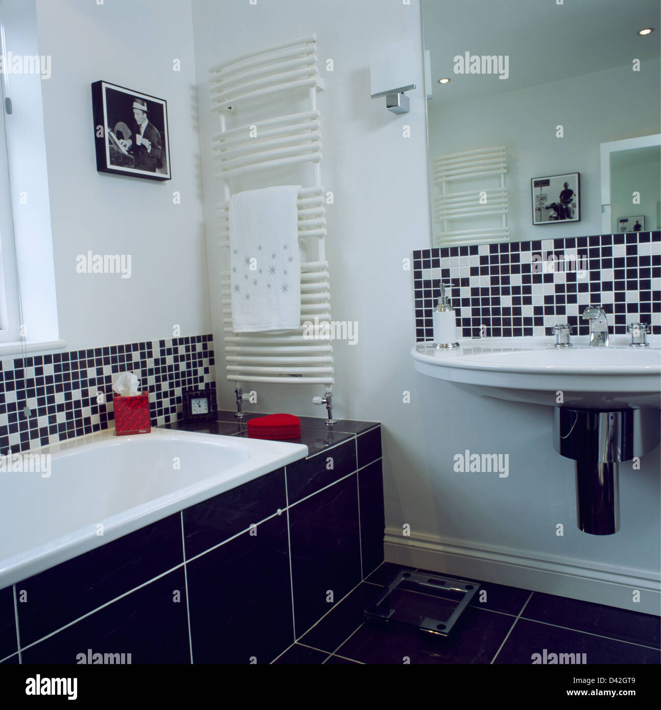 Black+white mosaic tiles above bath and basin in modern white Stock ...