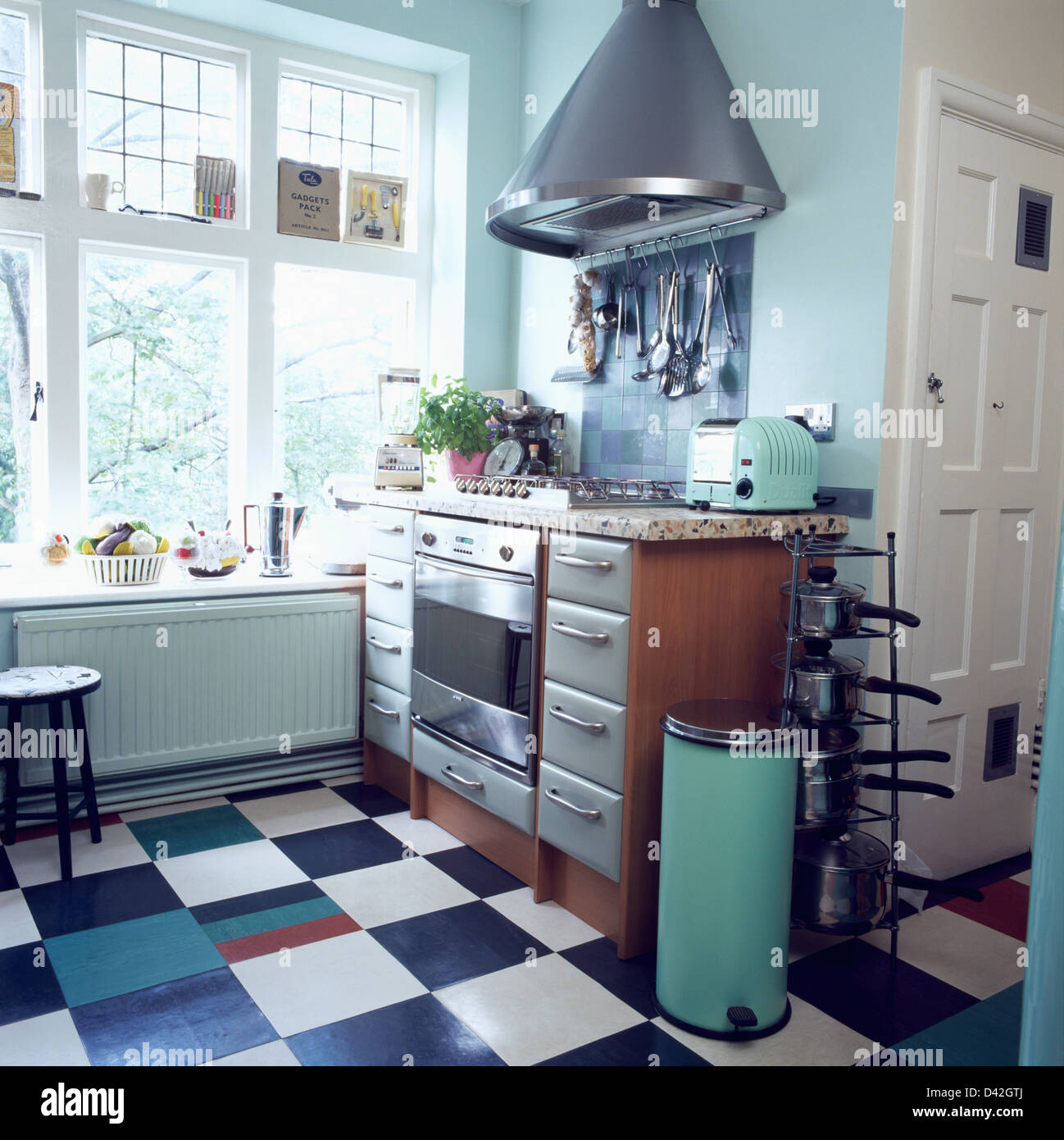 Chrome extractor above hob in pale turquoise kitchen with black+ ...