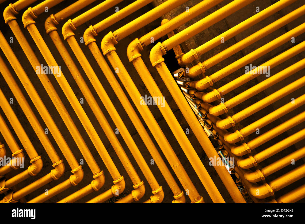 An image of yellow pipes forming an interesting pattern. - Stock Image