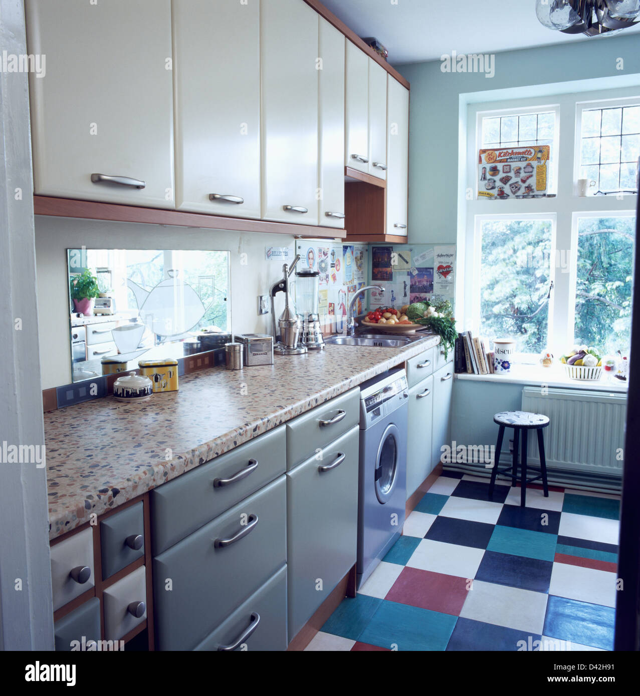 Colorful vinyl tiled floor in kitchen with Corian worktop on pale ...