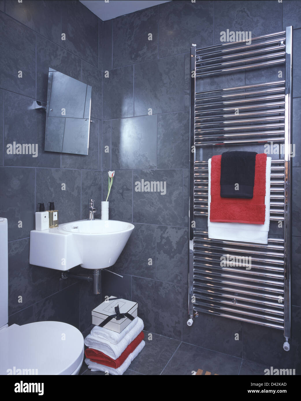 Wall-mounted basin and vertical chrome radiator in slate tiled Stock ...