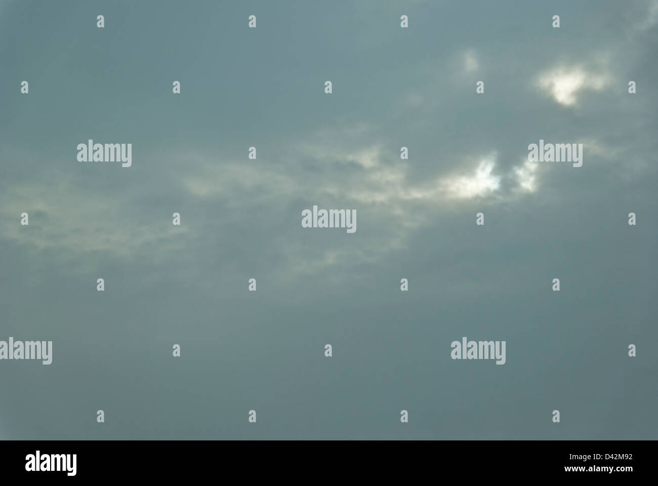 Overcast WInter sky with the sun breaking through snow clouds. - Stock Image