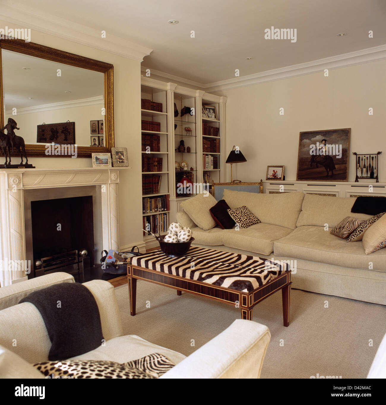 attractive Living Room With Cream Sofa Part - 15: Zebra print stool and cream sofa in elegant living room with large mirror  above marble fireplace between fitted bookcases