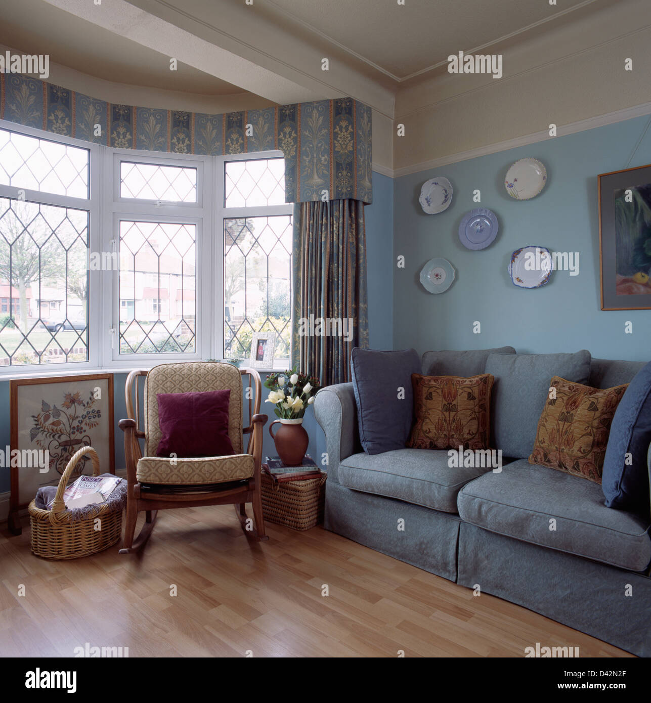 Rocking Chair In Front Of Bay Window With Blue Drapes In