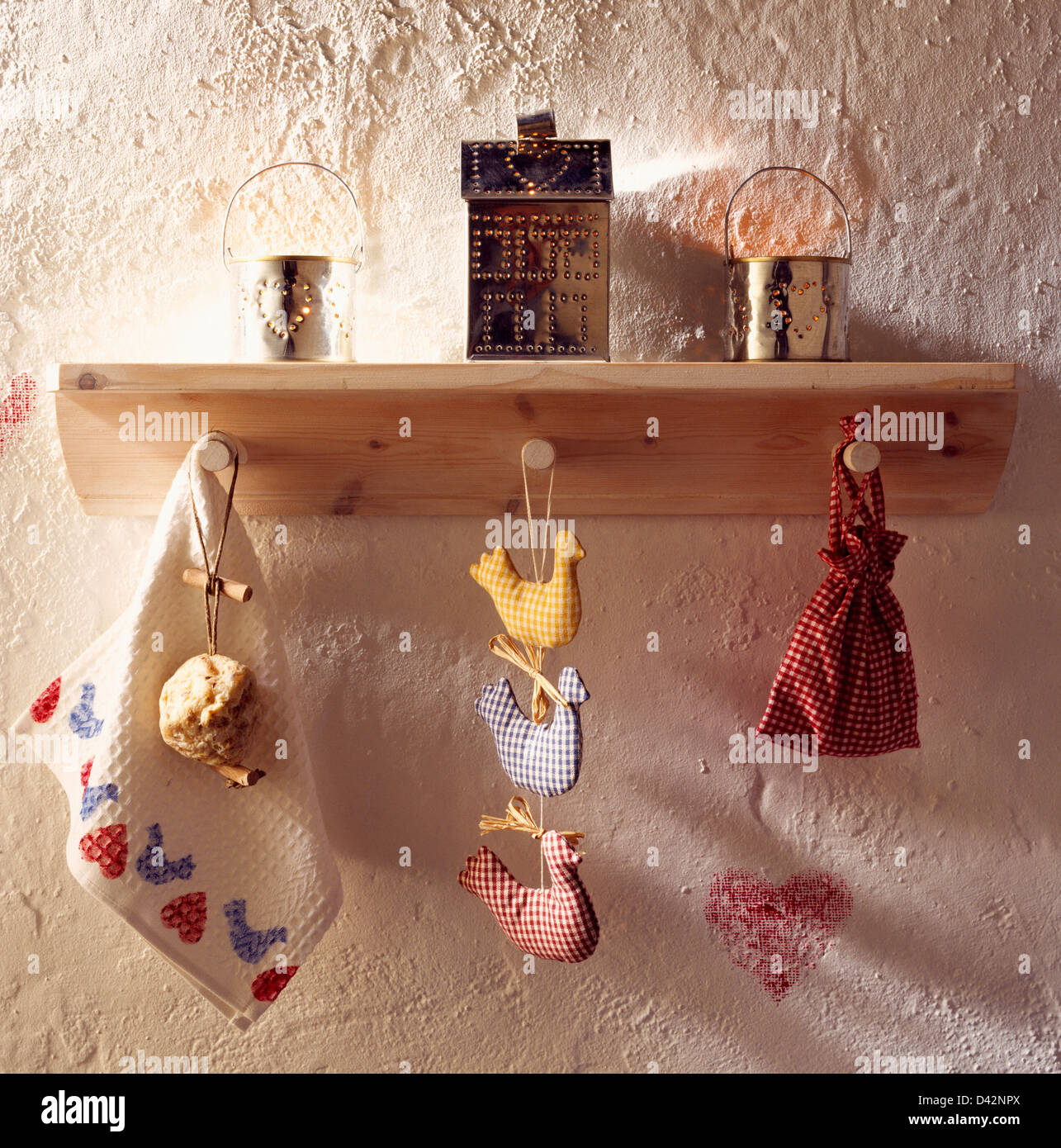Close-up of punched tin candle holders on wooden shelf with Shaker-style gingham bag and cloth ducks on peg rail - Stock Image