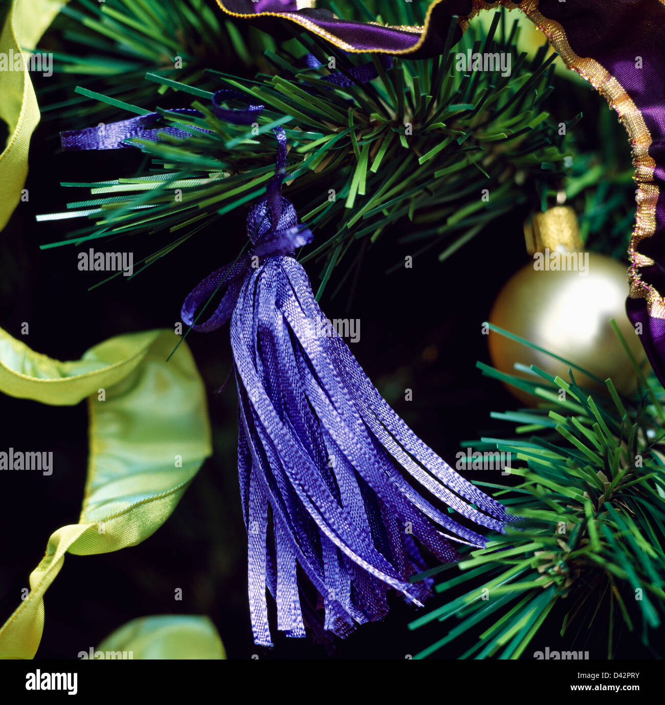 close up of blue silk tassel on faux christmas tree branch with gold bauble and - Lime Green And Blue Christmas Decorations