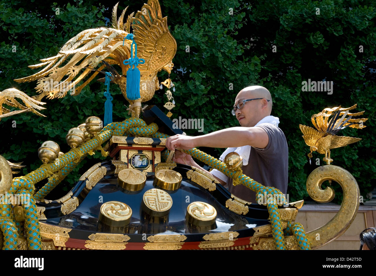 An artisan fastens gold ornaments while decorating a mikoshi portable shrine for the Sanja Matsuri Festival in Asakusa, - Stock Image