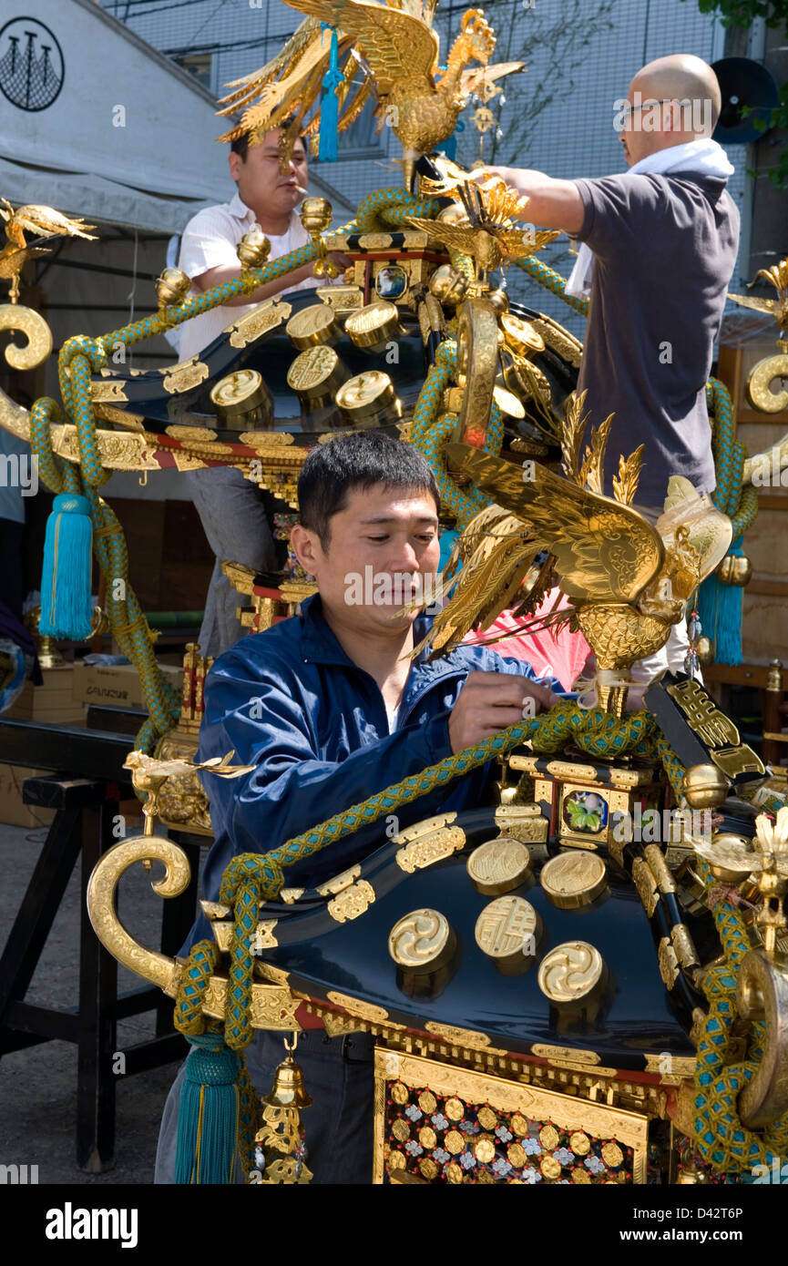 Artisans fasten gold ornaments while decorating a mikoshi portable shrine for the Sanja Matsuri Festival in Asakusa, - Stock Image