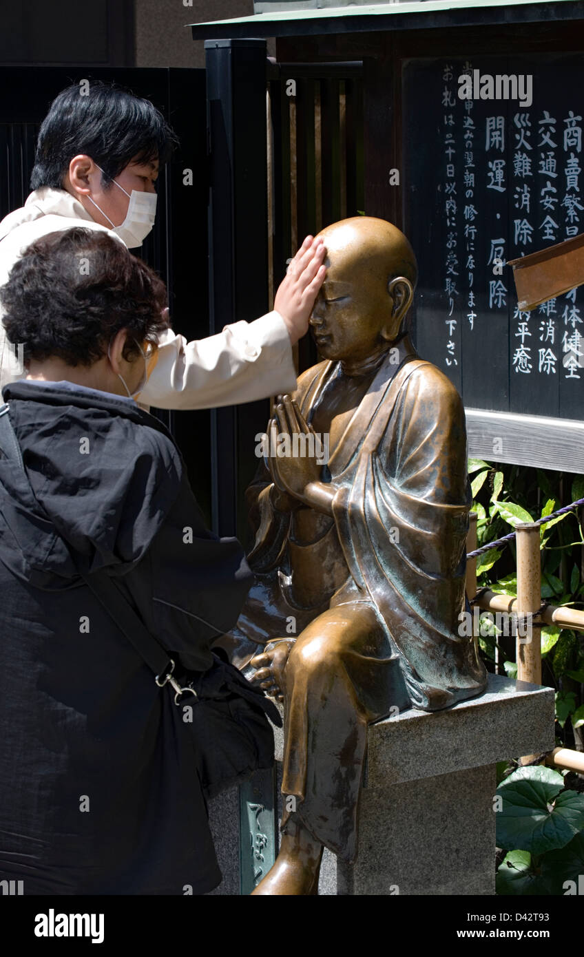 Worshipers rub and touch a sacred bronze Buddha statue at Sensoji Temple in Tokyo hoping to cure their physical - Stock Image