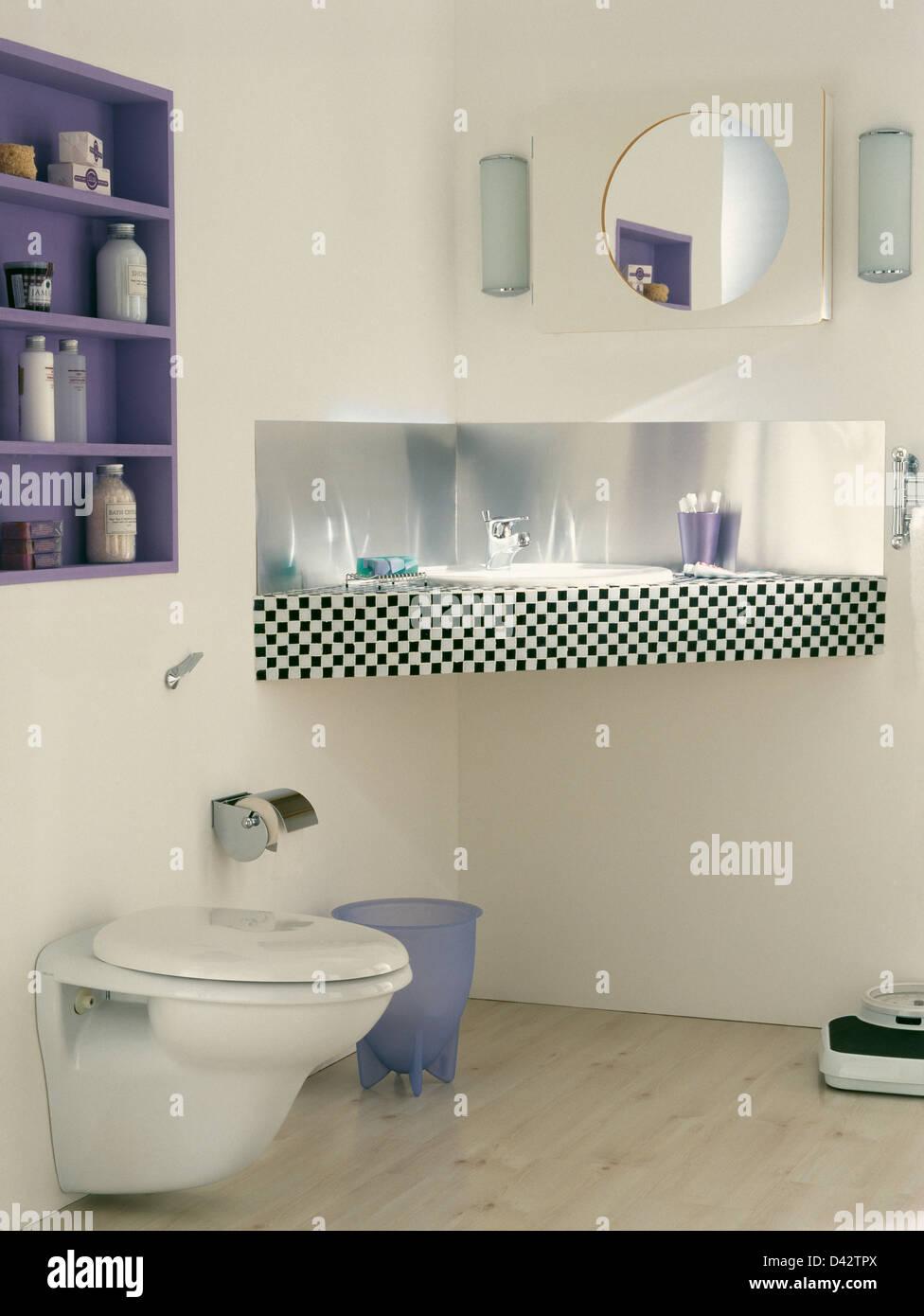 Stainless-steel splash back and black+white tiled edging on vanity ...