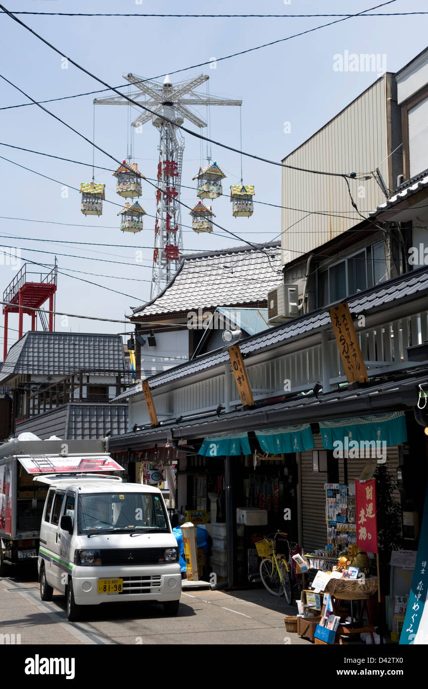 An amusement park merry-go-round towers high above retail shops in the old entertainment district of Asakusa, Tokyo. - Stock Image