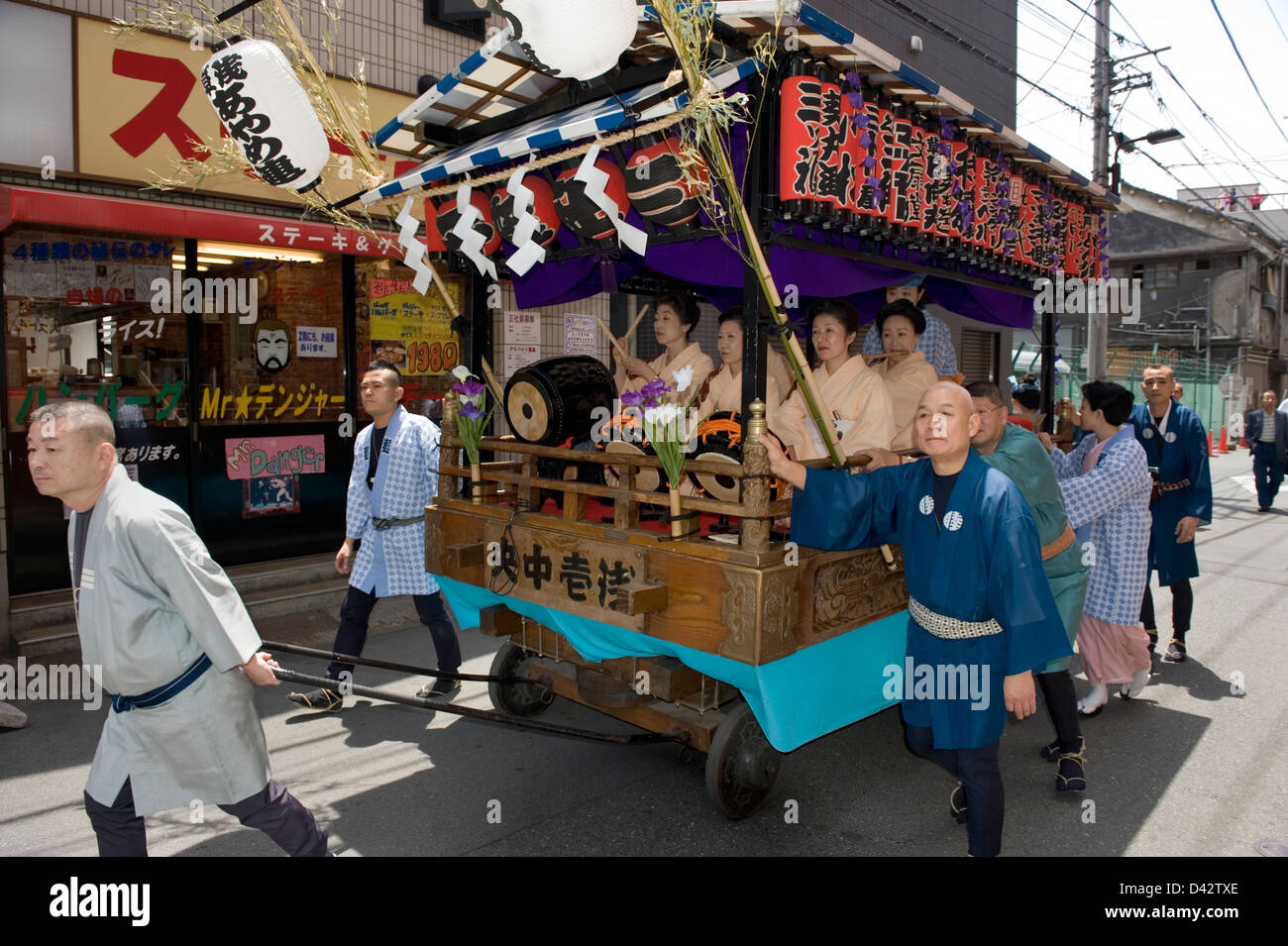 Wagon carrying female musicians wearing traditional kimono is pulled through a neighborhood during Sanja Matsuri - Stock Image