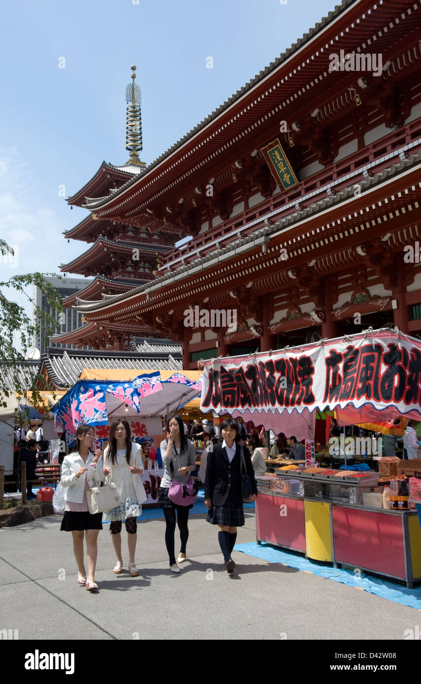Group of girls walking past festival roten stands set up in front of Sensoji Temple in Asakusa, Tokyo. - Stock Image