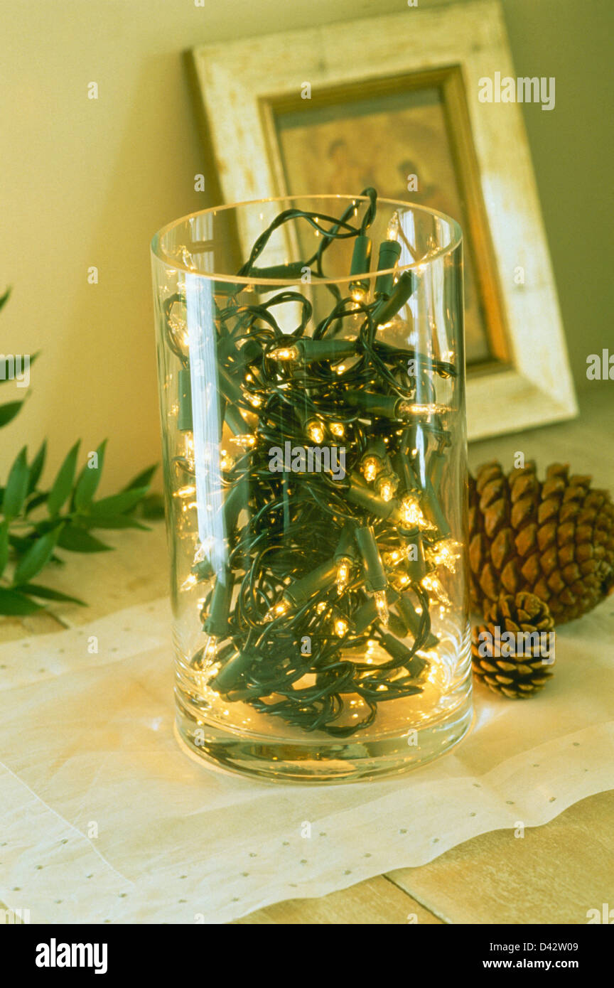 Close-up of miniature Christmas lights in cylindrical glass vase ...