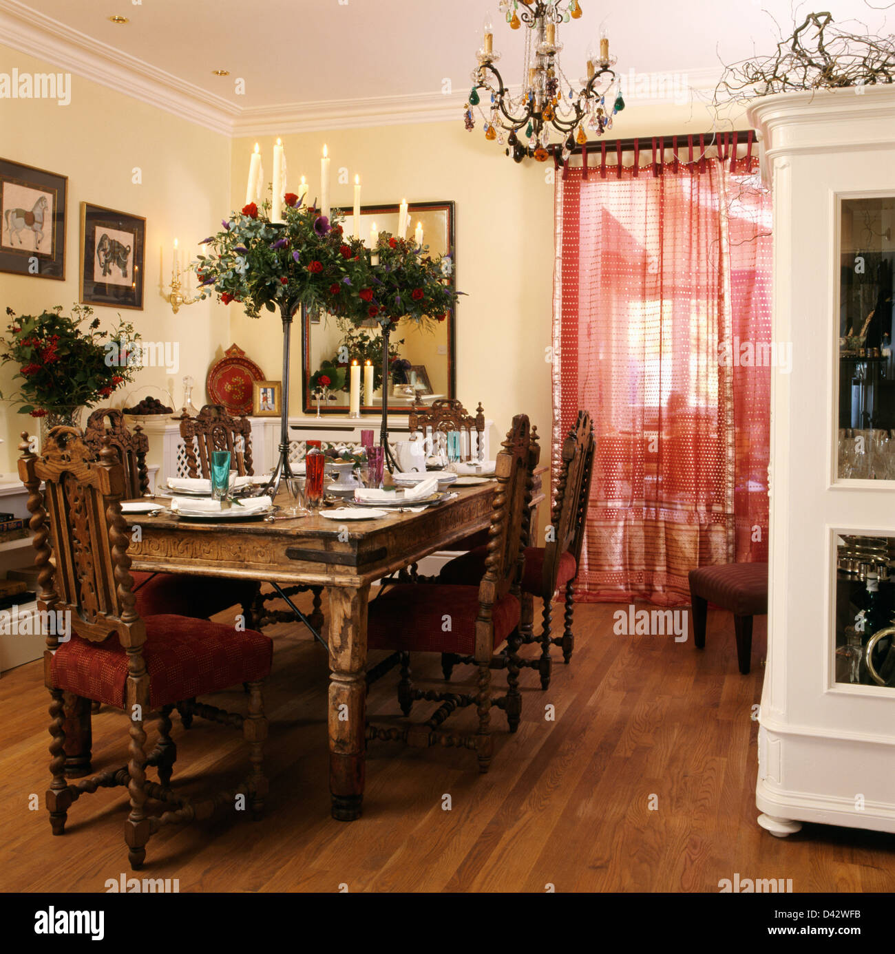 Jacobean-style chairs at renovated table with tall foliage displays in dining room with red Sari fabric door-curtain Stock Photo