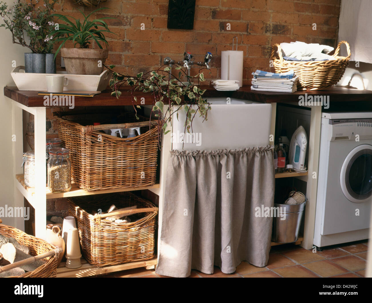 Superbe Storage Baskets On Shelf Unit Beside Belfast Sink In Unit With Gray Curtain  In Rustic Country Utility Room