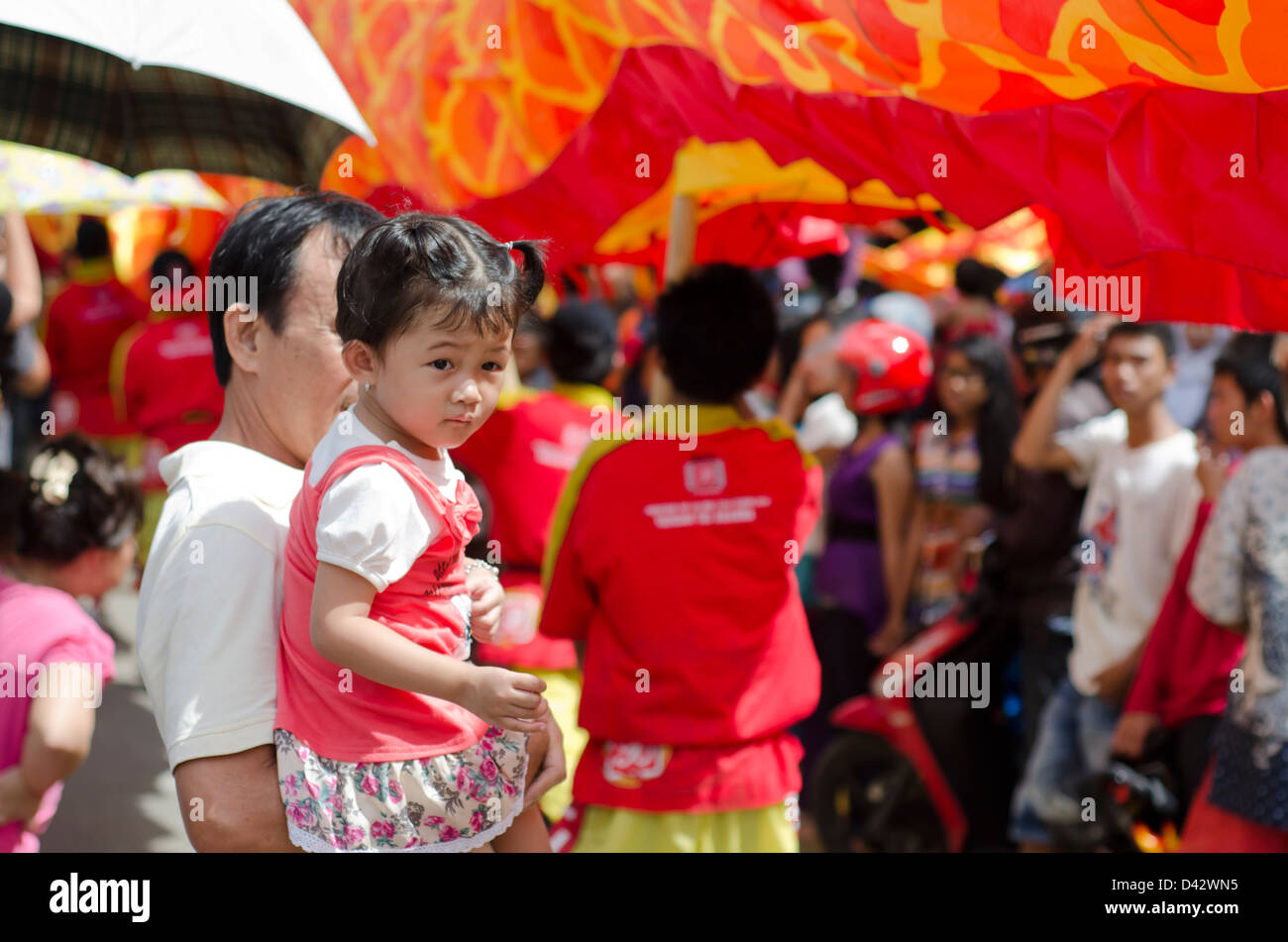 Small Chinese girl watching Chinese New Year celebrations, West Kalimantan, Indonesia. - Stock Image
