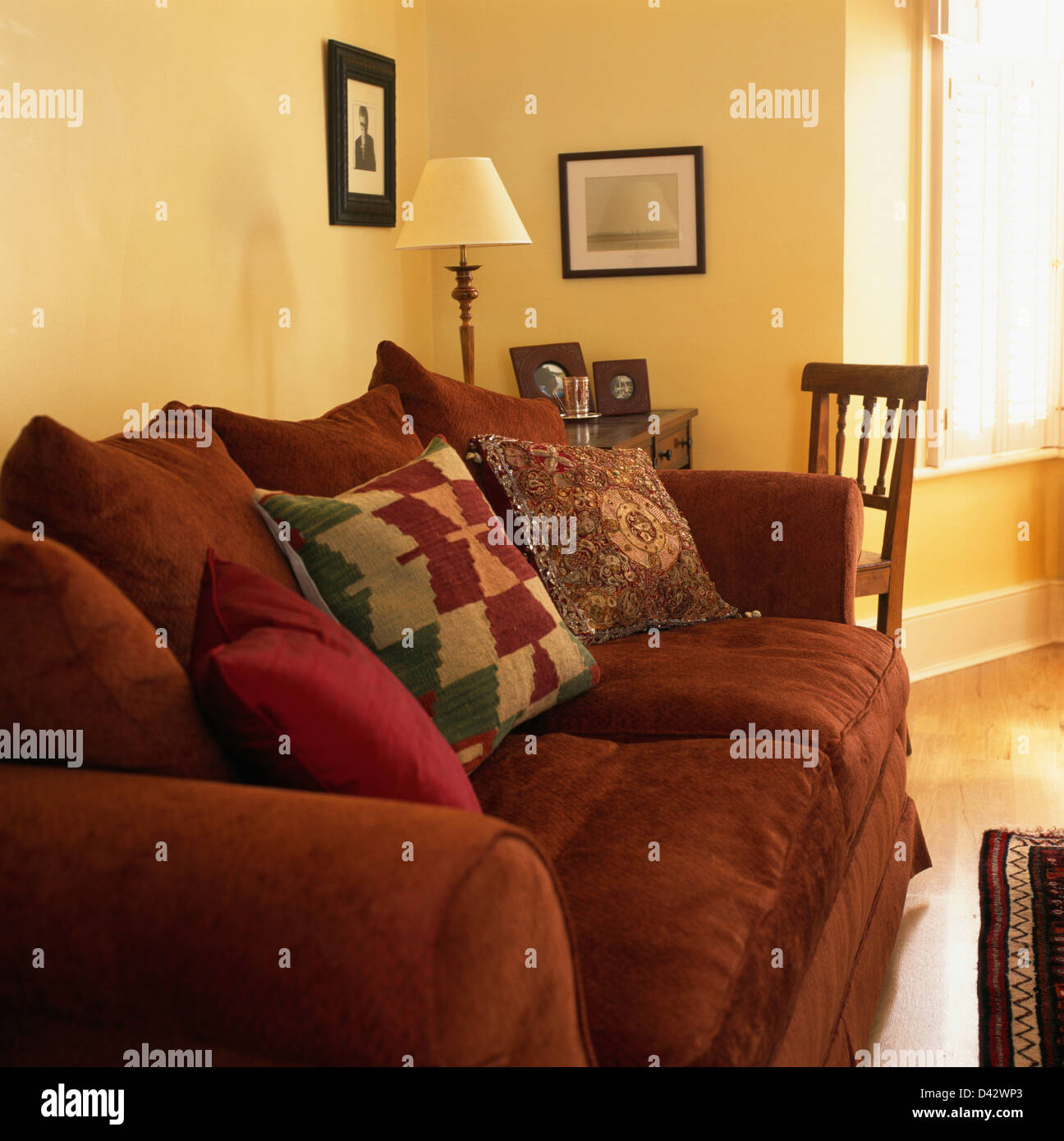 R Patterned Cushions On Rust Colored Sofa In Traditional Living Room