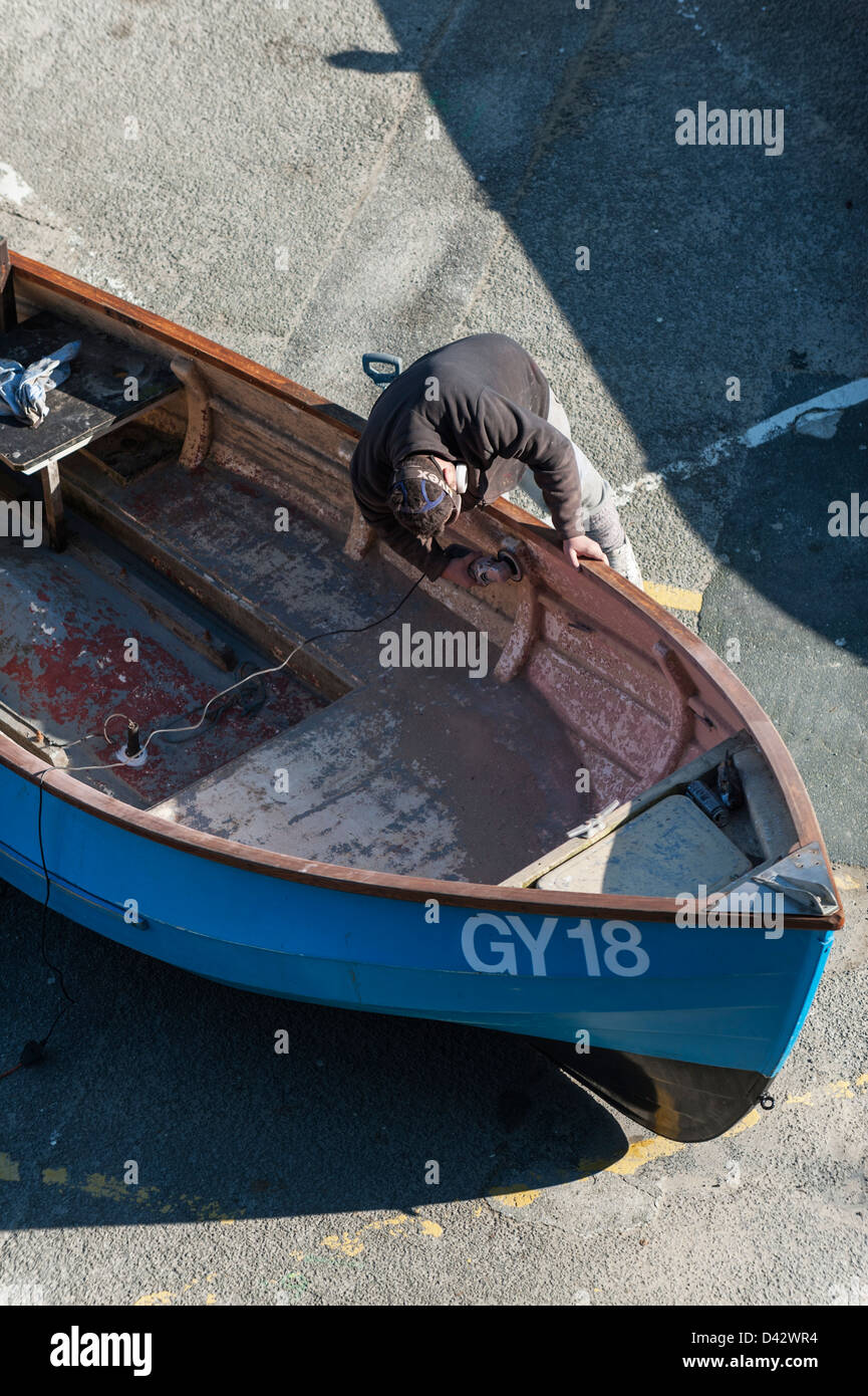 A man refurbishing a dinghy. - Stock Image
