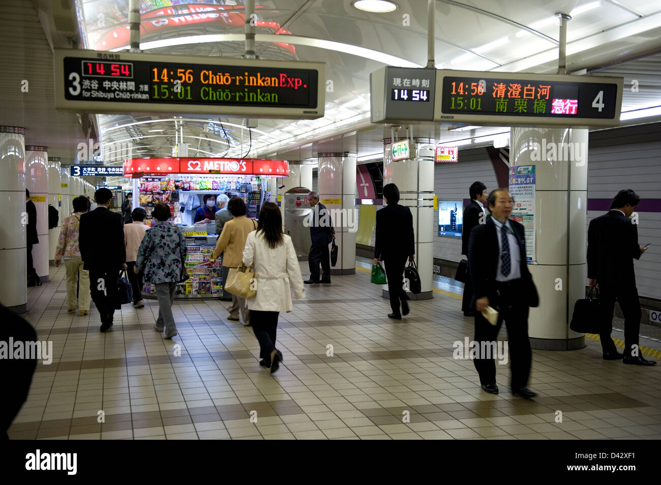 People walking around on a Tokyo Metro subway underground platform while waiting for the train to arrive. - Stock Image