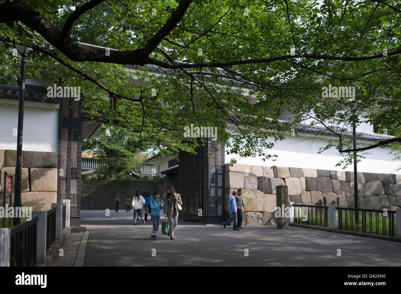 People passing through the old Edo Castle stone wall and gate at the outer moat in Chiyoda-ku, Tokyo. - Stock Image