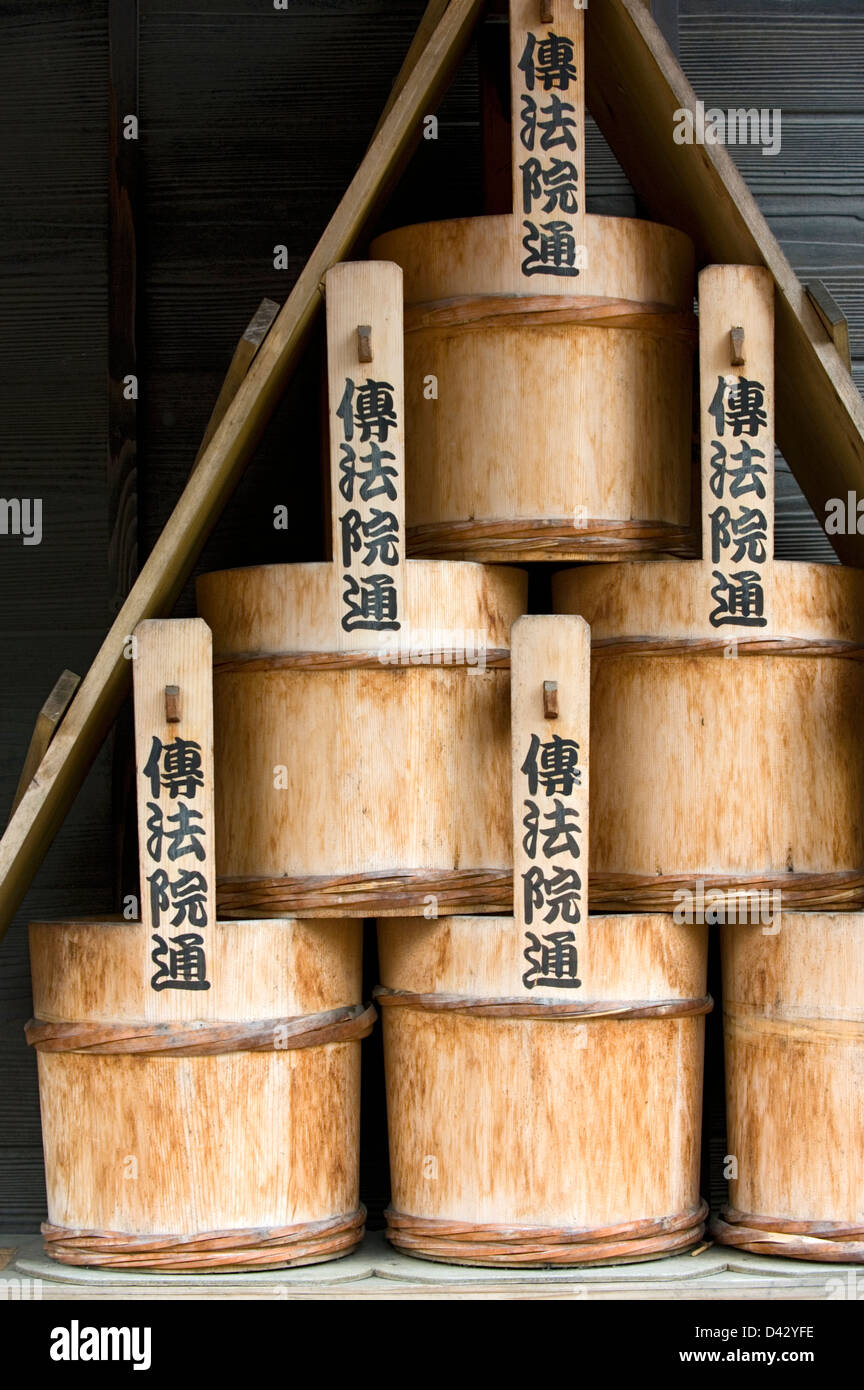 A stack of old traditional wooden water buckets for putting out fires at a temple in Tokyo. Stock Photo