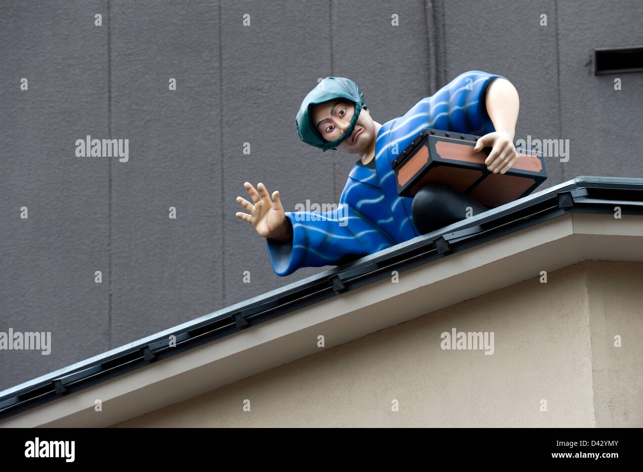 Thief wearing traditional attire escaping across building roof is caught in the act of stealing a treasure in Asakusa, - Stock Image