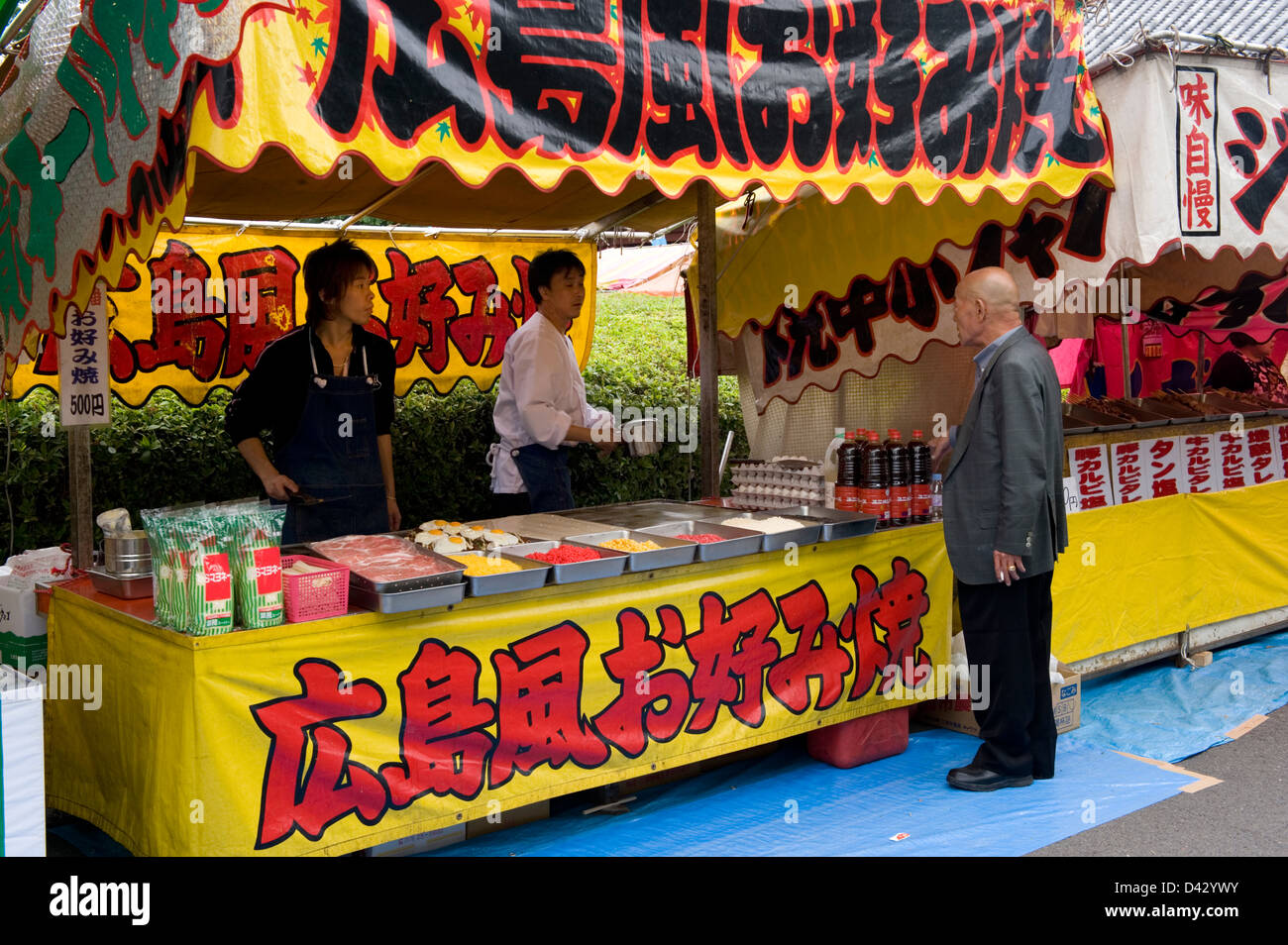 Roten stand is selling famous Hiroshima okonomiyaki, a Japanese pizza with cabbage, meat and eggs, at a festival - Stock Image