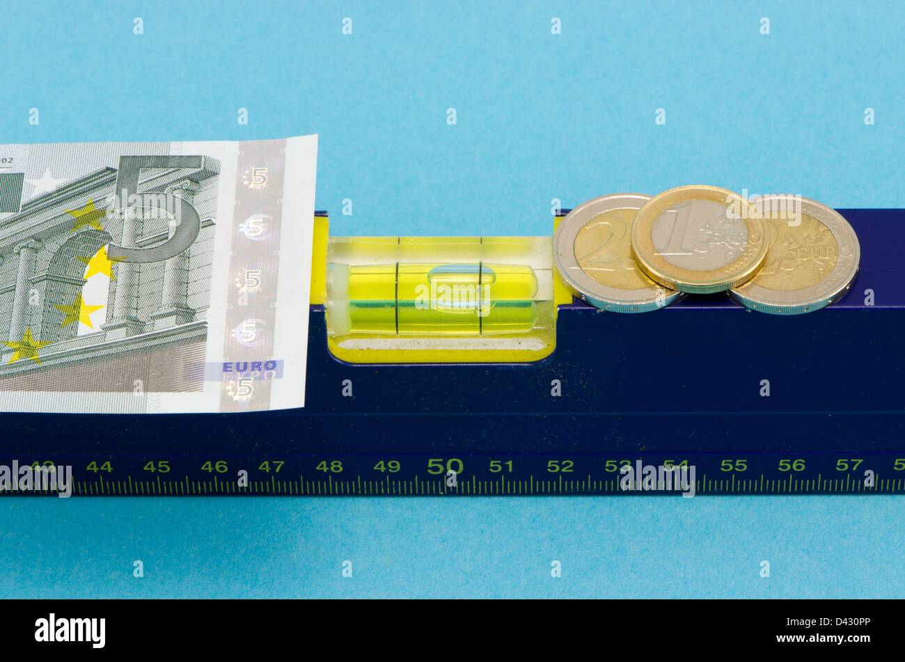 construction industry spirit level tool euro banknote and coins on blue background. - Stock Image