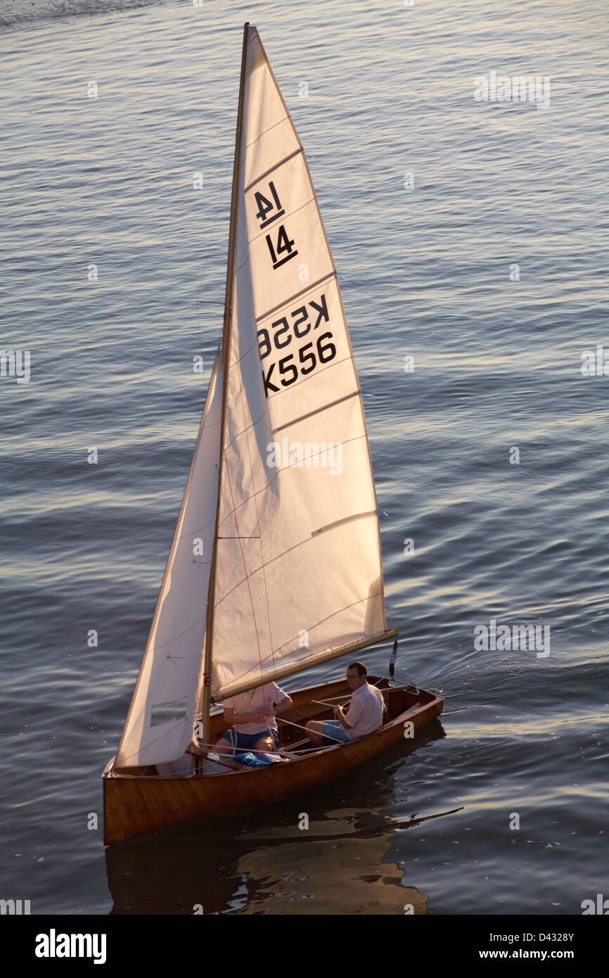 sailing yacht with evening light shining through the sails in September - Stock Image