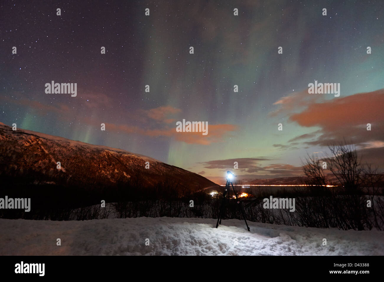 tripod and camera set up to photograph swirling northern lights aurora borealis near tromso in northern norway europe - Stock Image