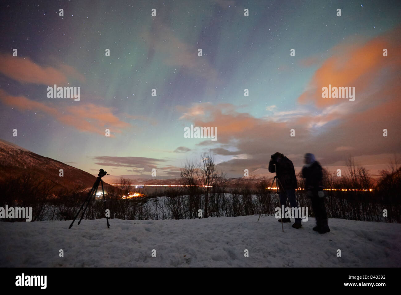 tourists with tripod and camera set up to photograph swirling northern lights aurora borealis near tromso in northern - Stock Image