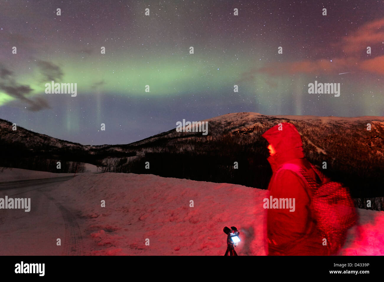 tourist photographer with tripod and camera set up to photograph swirling northern lights aurora borealis near tromso - Stock Image