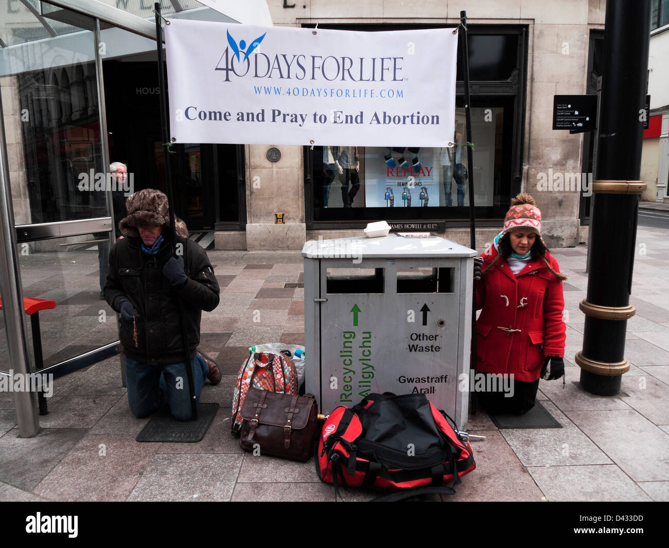 Anti abortion pro life protesters praying on knees with 40 days for life banner St. Mary Street Cardiff Wales UK - Stock Image