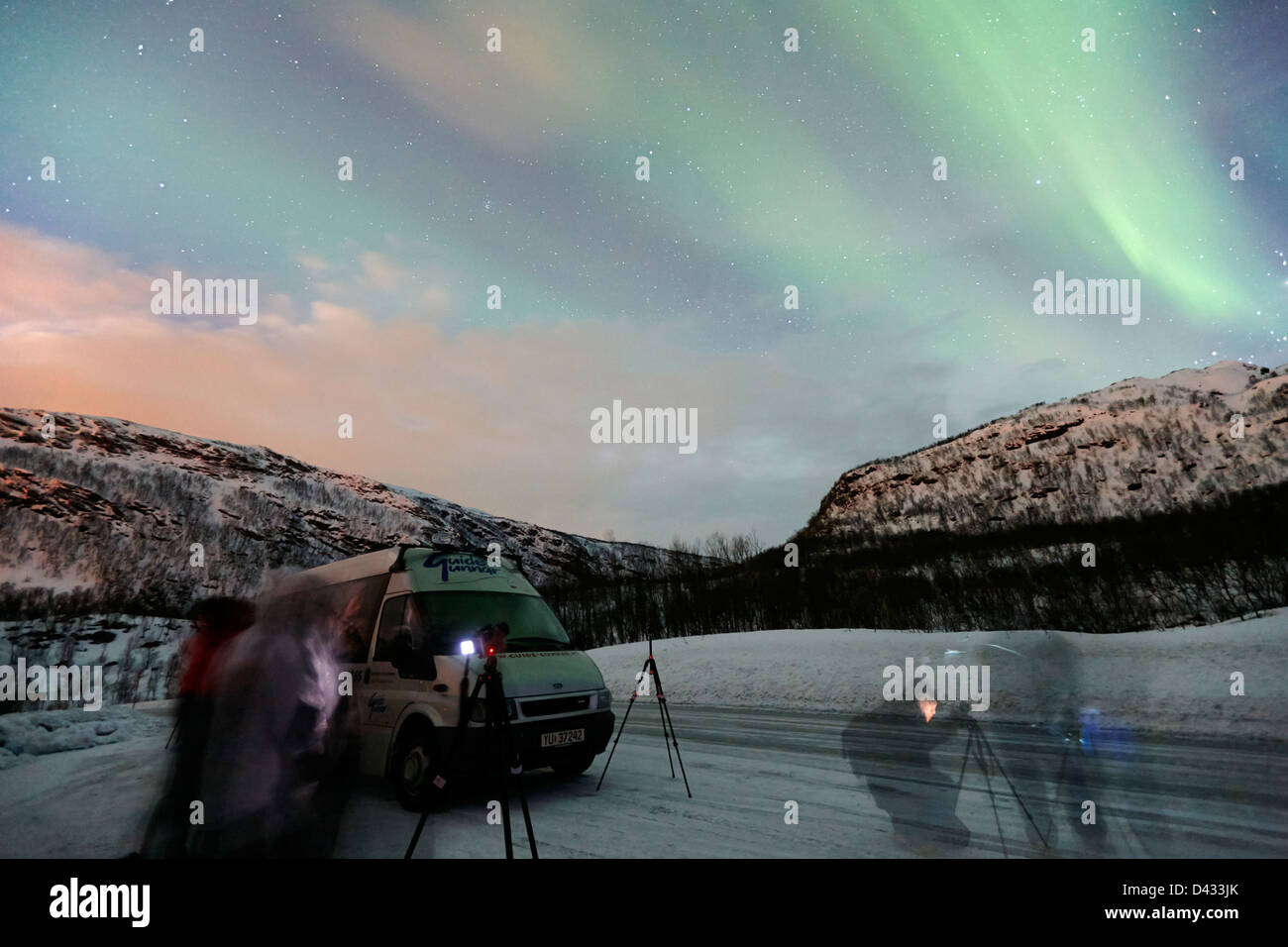 group of tourists set up to photograph swirling northern lights aurora borealis near tromso in northern norway europe - Stock Image