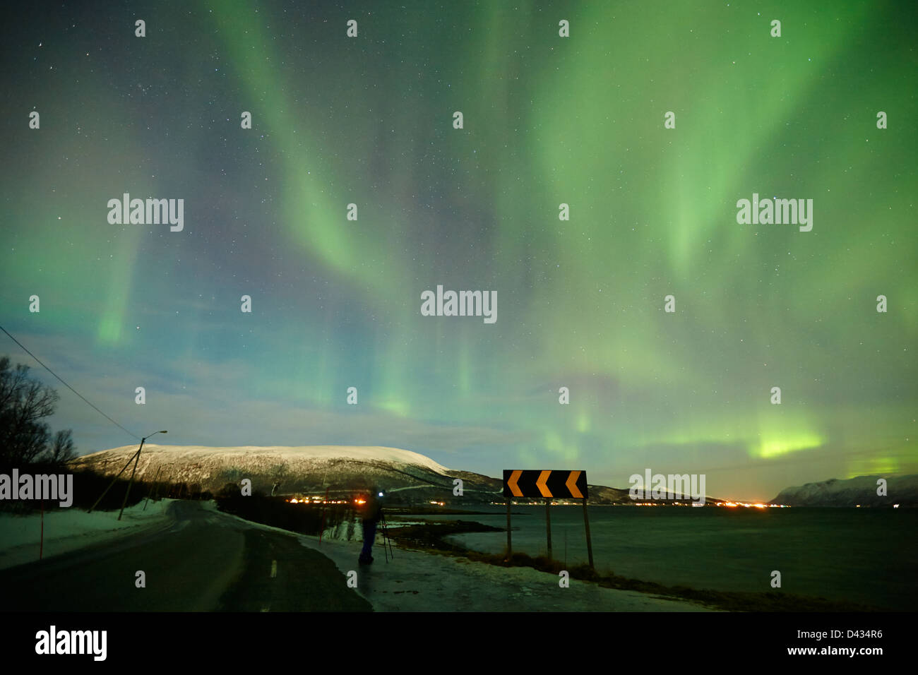 lone photographer takes photos of swirling northern lights aurora borealis over fjord near tromso in northern norway - Stock Image