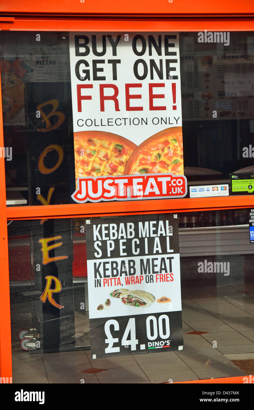 Poster advertising buy one get one free in food shop window Stock